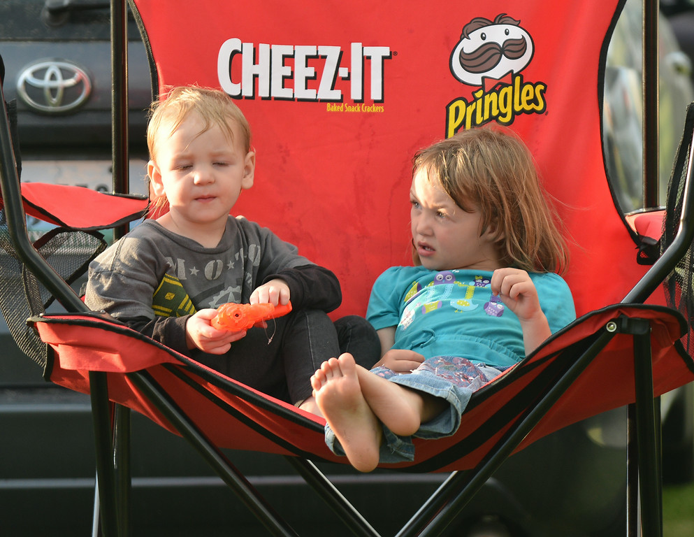 Two-year-old Dillon Roberts, left, and Jadin Roberts, 4, hang out in an over sized folding chair as they wait for the sun to go down during the fireworks celebration Friday evening at the Big Horn Equestrian Center.