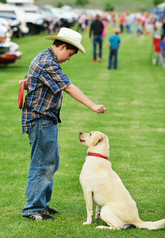 Eleven-year-old Nathan Gearhart exercises his dog Asher with a Frisbee during the fireworks celebration Friday evening at the Big Horn Equestrian Center.