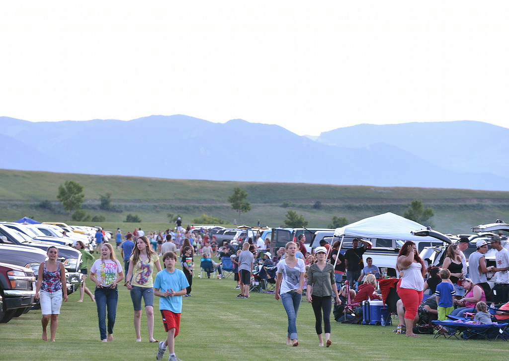 People move between parked vehicles during the fireworks celebration Friday evening at the Big Horn Equestrian Center.