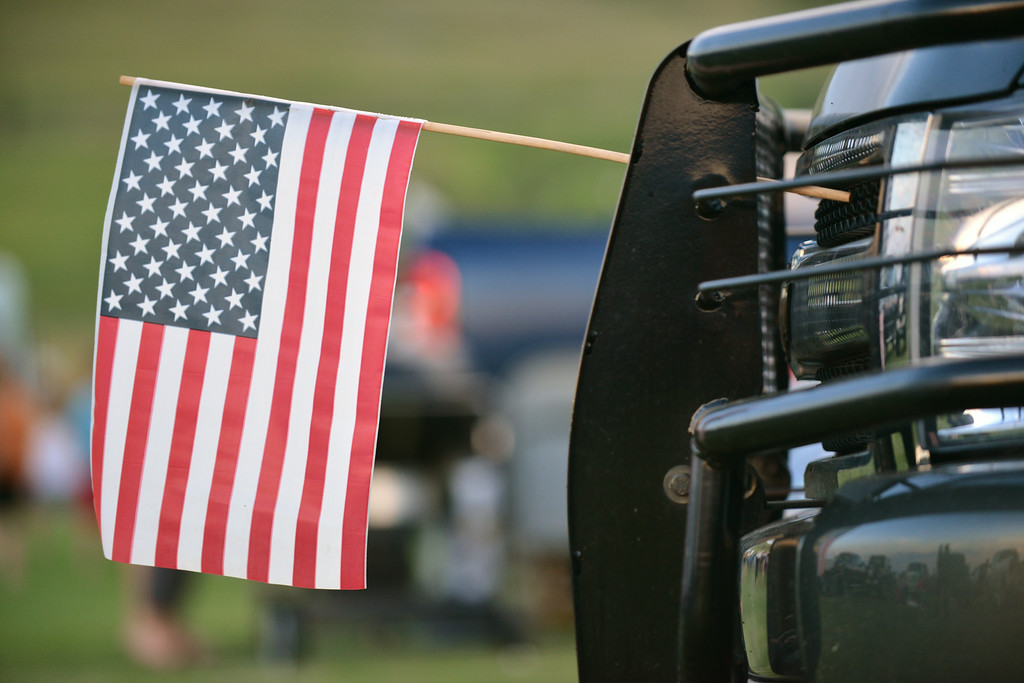 The National Flag is displayed from the grill of a pickup truck during the fireworks celebration Friday evening at the Big Horn Equestrian Center.
