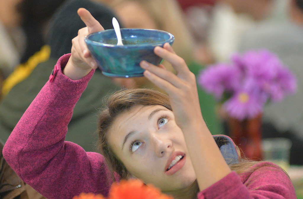 Justin Sheely | The Sheridan Press<br /> Sheridan high school student Grace Von Krosigk looks for a name under her bowl during the VOA's Empty Bowl chili dinner fundraising event Thursday at the Sheridan County Fairgrounds exhibit hall. The bowls were crafted by Sheridan County students. The event benefits the Sheridan Community Shelter. This year's event saw record breaking attendance with more than 850 guests.