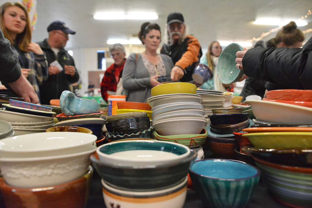 Justin Sheely | The Sheridan Press<br /> Guests pick over ceramic bowls made by local students during the VOA's Empty Bowl chili dinner fundraising event Thursday at the Sheridan County Fairgrounds exhibit hall. The event benefits the Sheridan Community Shelter. This year's event saw record breaking attendance with more than 850 guests.