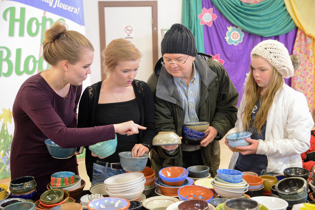 Justin Sheely | The Sheridan Press<br /> The Bateman family, from left, Bailey, Brynn, Scott and Tate pick out bowls for their chili during the VOA's Empty Bowl chili dinner fundraising event Thursday at the Sheridan County Fairgrounds exhibit hall. The event benefits the Sheridan Community Shelter. This year's event saw record breaking attendance with more than 850 guests.