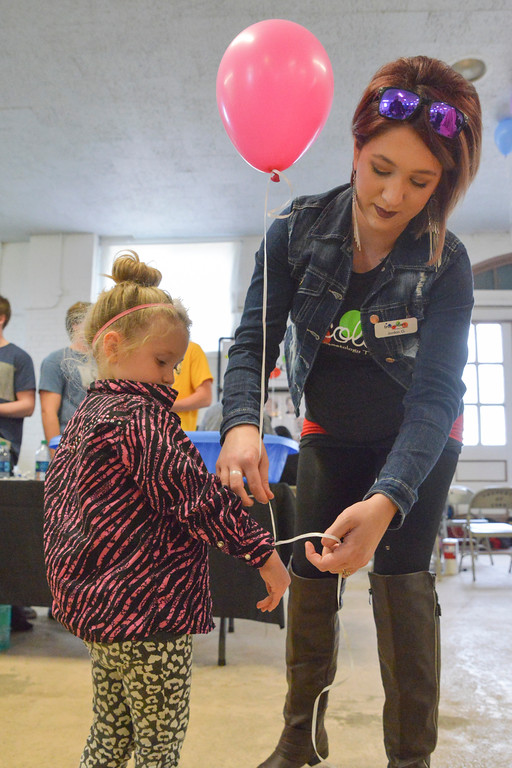 Justin Sheely | The Sheridan Press<br /> Jordan Gunnesl ties a balloon on her three-year-old daughter JayceeRay Gunnesl during the VOA's Empty Bowl chili dinner fundraising event Thursday at the Sheridan County Fairgrounds exhibit hall. The event benefits the Sheridan Community Shelter. This year's event saw record breaking attendance with more than 850 guests.