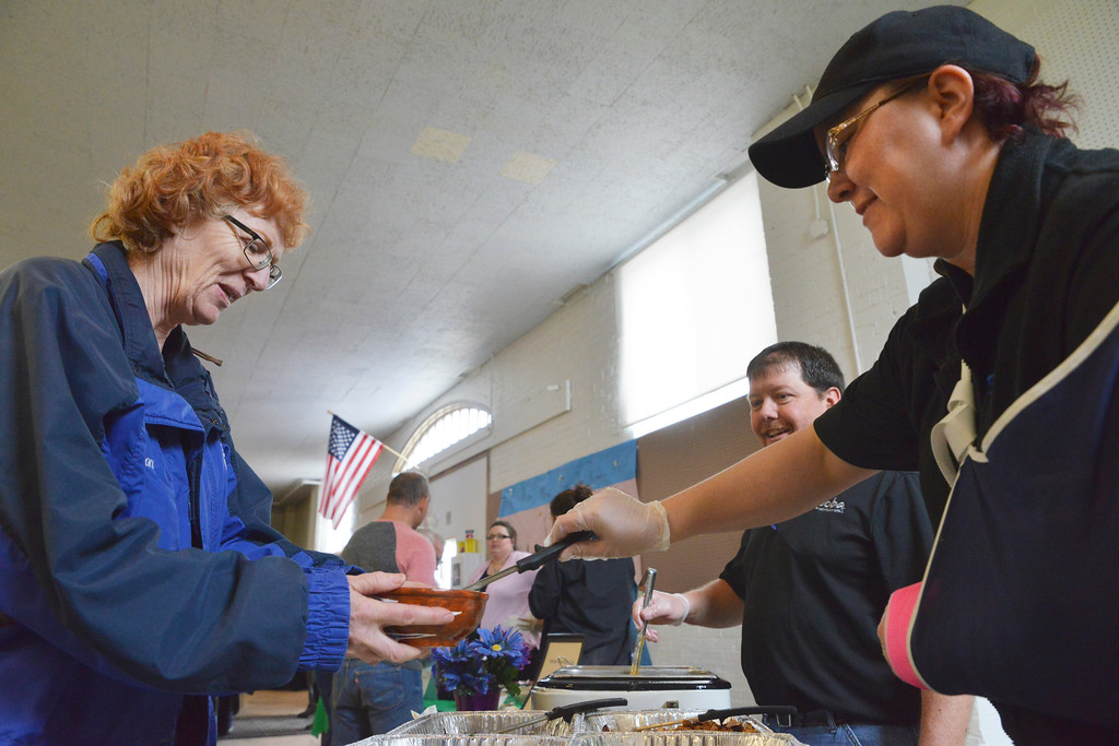 Justin Sheely | The Sheridan Press<br /> Jackie Jackson, left, receives her fill from Qdoba's Kristina Parker during the VOA's Empty Bowl chili dinner fundraising event Thursday at the Sheridan County Fairgrounds exhibit hall. The event benefits the Sheridan Community Shelter. This year's event saw record breaking attendance with more than 850 guests.