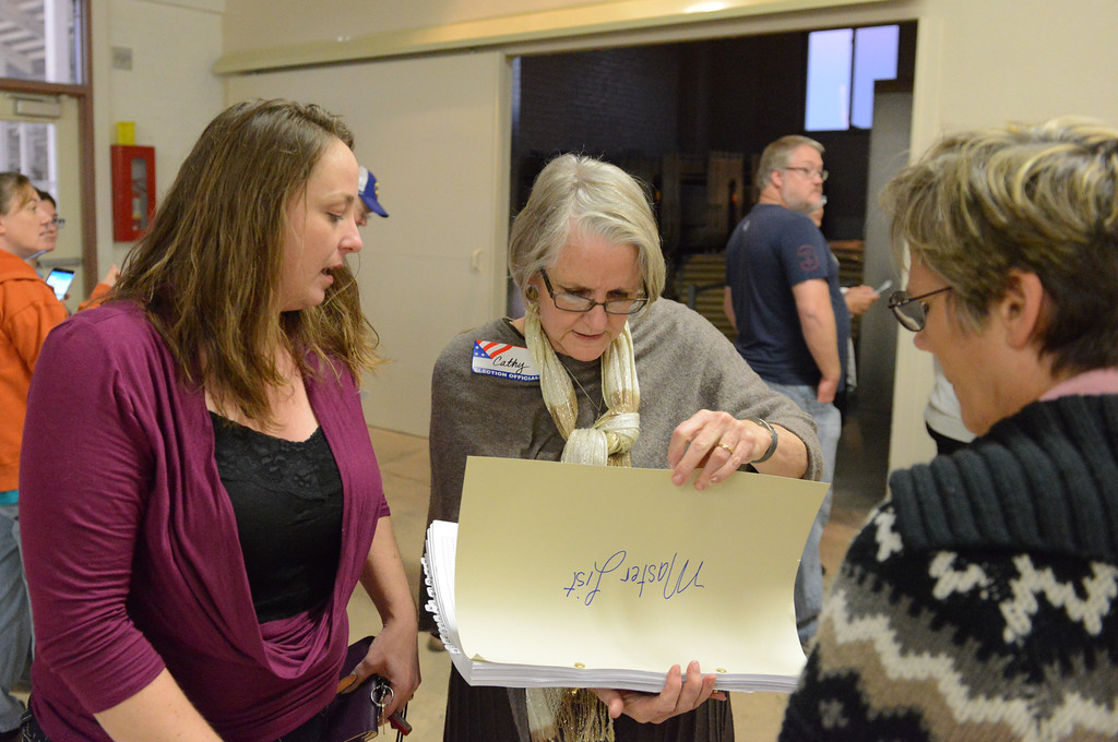 Justin Sheely | The Sheridan Press<br /> Amber McHoes, left, watches as election official Cathy Paullin double checks her name on the list of voters Tuesday night at the Sheridan County Fairgrounds. McHoes waited in line for nearly half hour before she was told she was at the wrong polling site.