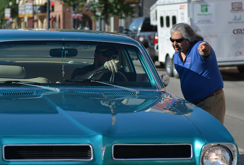 Justin Sheely | The Sheridan Press<br /> Volunteer Rene DeLuna directs a car owner to a space during the Karz Rod Run car show Saturday morning on Main Street. The show had more than 160 entries this year – one of the fullest in recent years.