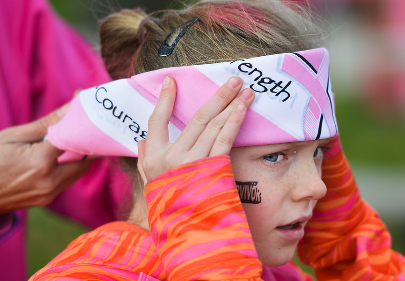 Justin Sheely   The Sheridan Press<br /> Ten-year-old Madalynn Dellit holds still as a bandana is tied around her head during The Link – Partners in Pink event Saturday at Whitney Commons.