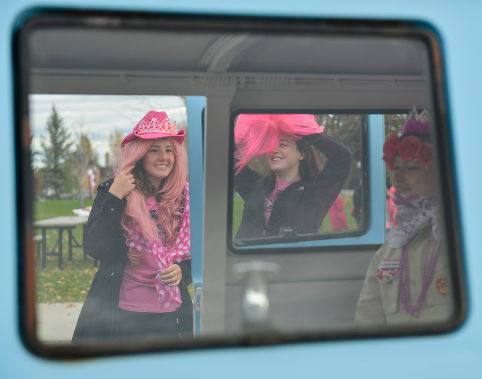 Justin Sheely | The Sheridan Press<br /> Libby Standish, left, and Zhoe Calkins put on costumes at the photobooth van during The Link – Partners in Pink event Saturday at Whitney Commons.