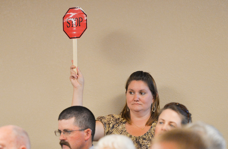 Justin Sheely | The Sheridan Press<br /> Teresa Detimore waves a signal as a candidate's time runs out during the Sheridan County of Commerce's Candidate Forum Tuesday night at the Sheridan Wesleyan Church.