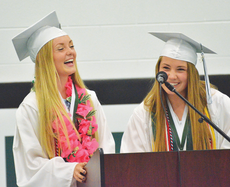 Mike Dunn | The Sheridan Press. <br /> Valedictorian LeeAnna Mitchell, left, and salutatorian Gracie Carr laugh during their joint speech at the Tongue River High School commencement ceremony Sunday.