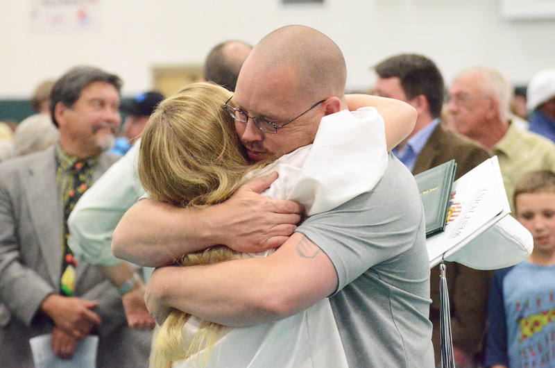 Mike Dunn | The Sheridan Press. <br /> Brian Mitchell, right, hugs his daughter LeeAnna at the Tongue River High School commencement ceremony Sunday.