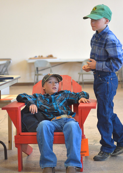 Justin Sheely | The Sheridan Press<br /> Ten-year-old Hardy Edwards, left, sits in a chair he built was his twin brother Will Edwards waits with him for the interviewing process of the static exhibit during the Sheridan County Fair Tuesday at the Sheridan County Fairgrounds Exhibit Hall.