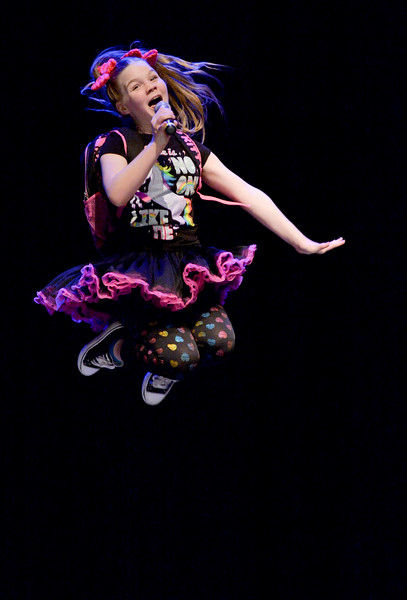 "Justin Sheely | The Sheridan Press<br /> Tate Bateman leaps in the air as she sings ""Kindergarten Love Song"" during the dress rehearsal for Stars of Tomorrow Thursday at the WYO Theater. The Sheridan Kiwanis Club talent contest is Friday, 7 p.m. at the WYO Theater."