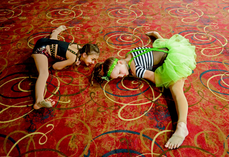 Justin Sheely | The Sheridan Press<br /> Eight-year-old Aslynn Maurer, left, stretches with Taylor Bower in the lobby during the dress rehearsal for Stars of Tomorrow Thursday at the WYO Theater. The Sheridan Kiwanis Club talent contest is Friday, 7 p.m. at the WYO Theater.