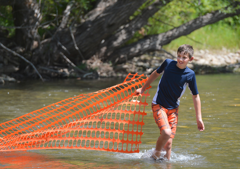 Justin Sheely | The Sheridan Press<br /> Twelve-year-old Brant Bockman pulls a makeshift rubber duck catcher from the Tongue River for the duck races during the 40th annual Dayton Days Saturday in the town of Dayton. The upper-ninety-degree weather did not stop Tongue River Valley residents from enjoying the day's festivities, including knocker ball, human foosball, duck races and the firemen's water fight.