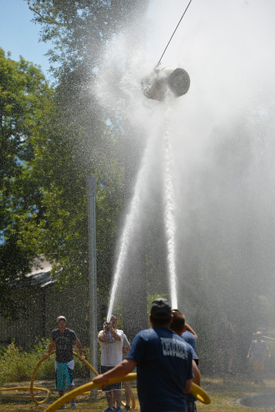 Justin Sheely | The Sheridan Press<br /> Teams aim their water streams at the suspended barrell to push against the other for the firemen's water fight during the 40th annual Dayton Days Saturday in the town of Dayton. The upper-ninety-degree weather did not stop Tongue River Valley residents from enjoying the day's festivities, including knocker ball, human foosball, duck races and the firemen's water fight.