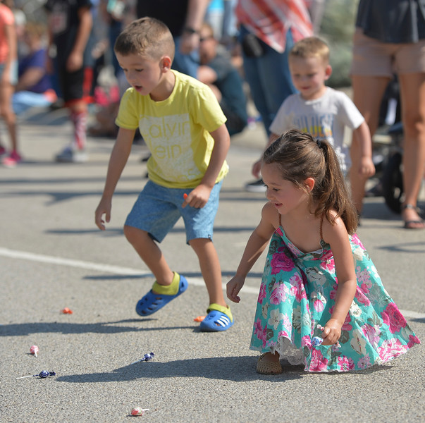 Justin Sheely | The Sheridan Press<br /> Five-year-old Augustus Nield, left, and Alivya Neeriemer, 4, gather candy during the parade at the 40th annual Dayton Days Saturday in the town of Dayton. The upper-ninety-degree weather did not stop Tongue River Valley residents from enjoying the day's festivities, including knocker ball, human foosball, duck races and the firemen's water fight.