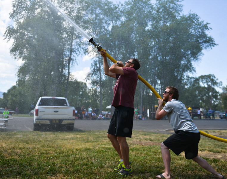 Justin Sheely | The Sheridan Press<br /> Patrick Mudd, left, and Cody Wojciechouski spray the suspended barrell for the firemen's water fight during the 40th annual Dayton Days Saturday in the town of Dayton. The upper-ninety-degree weather did not stop Tongue River Valley residents from enjoying the day's festivities, including knocker ball, human foosball, duck races and the firemen's water fight.