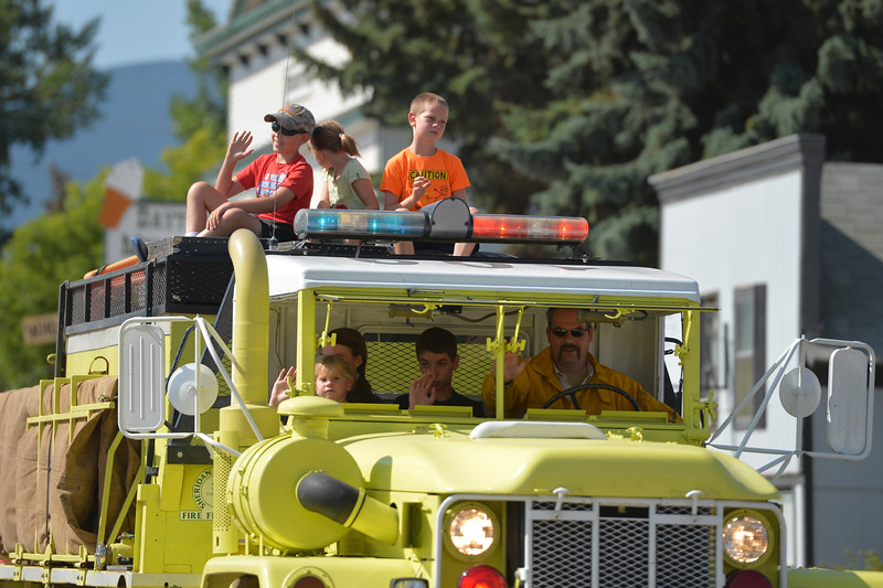 Justin Sheely | The Sheridan Press<br /> Kids wave at the audience from a Dayton volunteer fire truck for the parade during the 40th annual Dayton Days Saturday in the town of Dayton. The upper-ninety-degree weather did not stop Tongue River Valley residents from enjoying the day's festivities, including knocker ball, human foosball, duck races and the firemen's water fight.