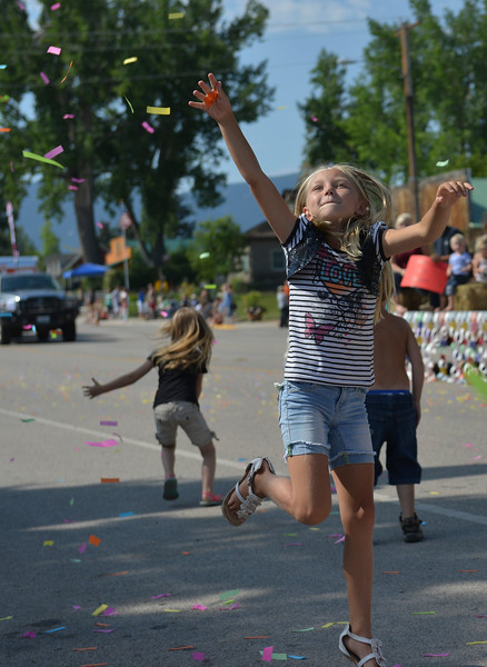 Justin Sheely | The Sheridan Press<br /> Eight-year-old Kaileigh Winder grabs at the floating confetti during the parade at the 40th annual Dayton Days Saturday in the town of Dayton. The upper-ninety-degree weather did not stop Tongue River Valley residents from enjoying the day's festivities, including knocker ball, human foosball, duck races and the firemen's water fight.