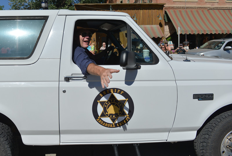 Justin Sheely | The Sheridan Press<br /> Robert Taylor – Sheriff Longmire – waves from his Ford Bronco during the Longmire Parade Friday in Buffalo. 2016 marks the 5th year of Longmire Days for the town of Buffalo, which hosted several events involving the cast and members of the crew to meet their fans. Longmire started out on cable television in 2012 and is now a series on Netflix. The show follows the exploits of Sheriff Walt Longmire in fictional Absaroka County, Wyoming. The series is from local author Craig Johnson's books, who based the fictional town in his books on Buffalo, Wyoming.