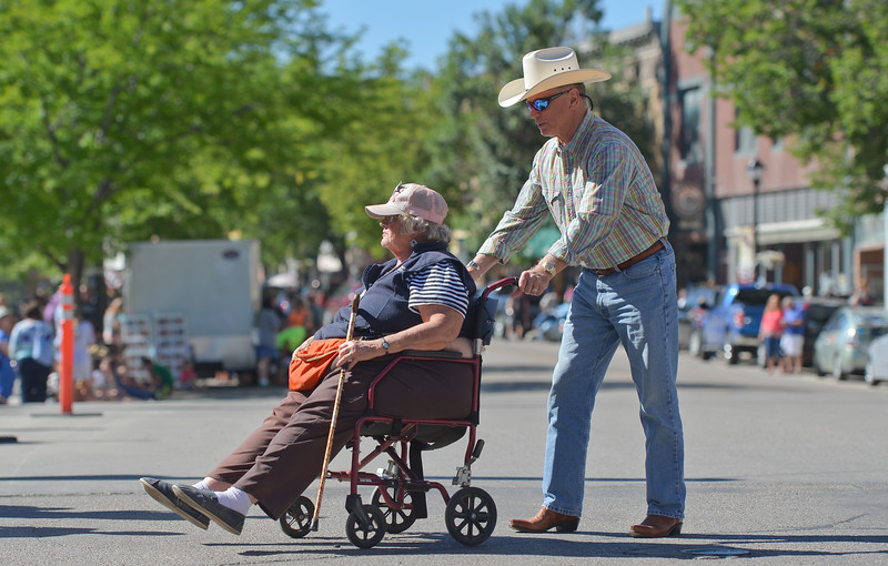 "Justin Sheely | The Sheridan Press<br /> Danny Neil of Victor, Idaho, helps Sheridan resident Donna Reed Jacobs across the street before the Longmire Parade Friday in Buffalo. ""I'm here to make sure [Walt Longmire] doesn't mess around with the Buffalo girls,"" Jacobs said. ""I'm like his mom."" 2016 marks the 5th year of Longmire Days for the town of Buffalo, which hosted several events involving the cast and members of the crew to meet their fans. Longmire started out on cable television in 2012 and is now a series on Netflix. The show follows the exploits of Sheriff Walt Longmire in fictional Absaroka County, Wyoming. The series is from local author Craig Johnson's books, who based the fictional town in his books on Buffalo, Wyoming."