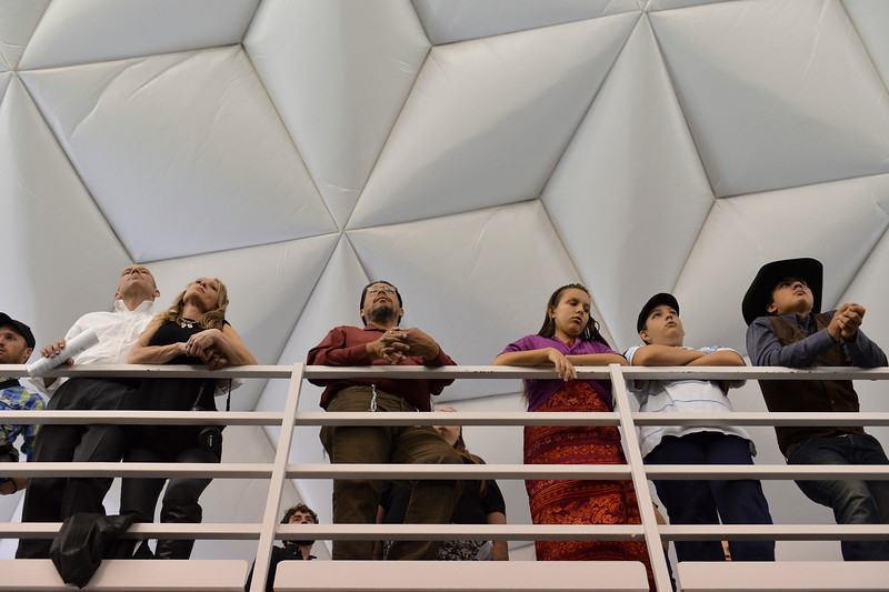 Justin Sheely | The Sheridan Press<br /> Graduate friends and families stand on the running track above during the 68th Commencement Ceremony Saturday in the Bruce Hoffman Golden Dome at Sheridan College.