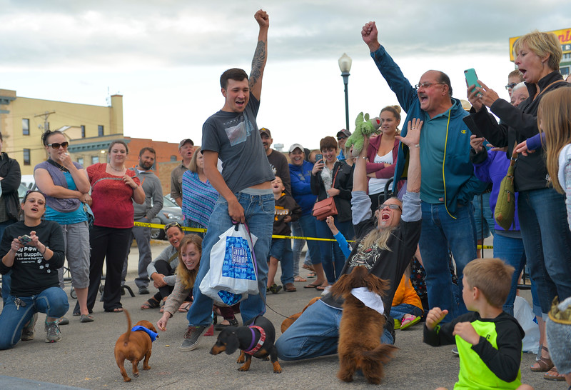 "Justin Sheely | The Sheridan Press<br /> Spunky's owner David Grimshaw, center, and friends celebrate after Spunky wins the ""Top Dog"" race during Muddy Paw Prints' annual Wiener Dog Races Tuesday evening at Blacktooth Brewing Company."
