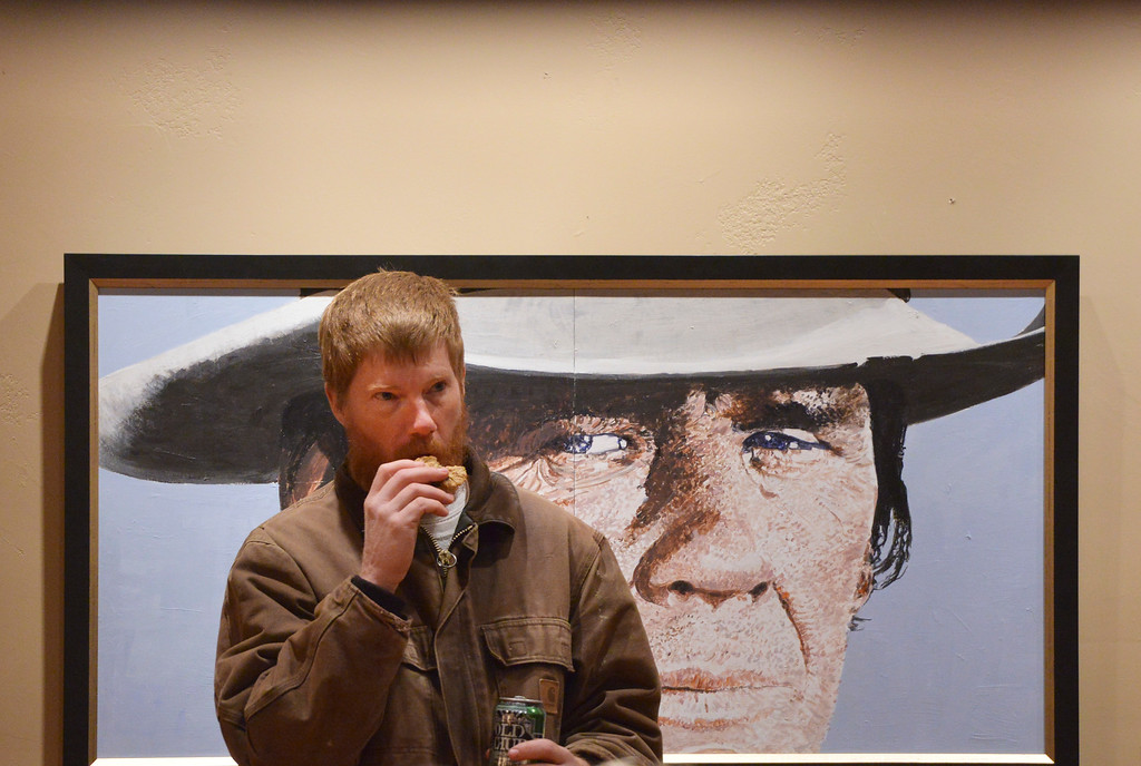 Justin Sheely | The Sheridan Press<br /> A man stands in front of a painting during the Ucross Christmas Celebration Saturday at the Raymond Plank Creative Center at Ucross. The event hosted treats, craft activities, Christmas carols and featured a reading Longmire author Craig Johnson. The fireworks show was canceled this year due to weather concerns.