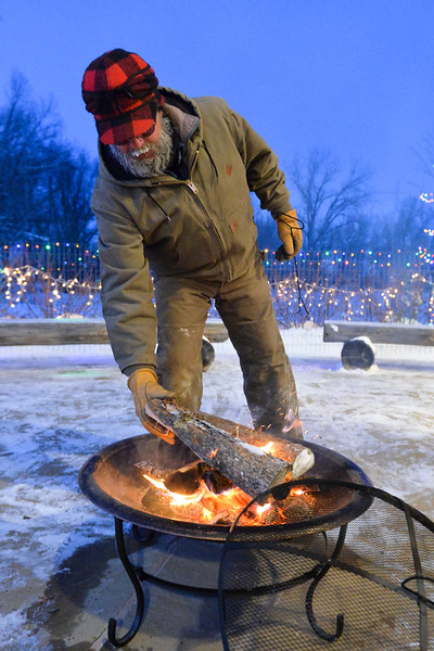 Justin Sheely | The Sheridan Press<br /> Marty Jelly of the Ucross maintenance staff feeds the fire pit outside during the Ucross Christmas Celebration Saturday at the Raymond Plank Creative Center at Ucross. The event hosted treats, craft activities, Christmas carols and featured a reading Longmire author Craig Johnson. The fireworks show was canceled this year due to weather concerns.