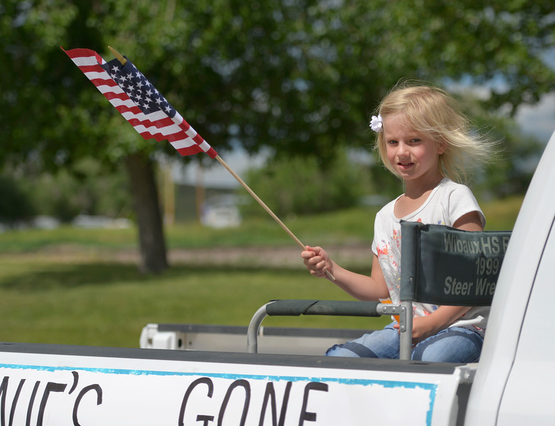 Justin Sheely | The Sheridan Press<br /> Five-year-old Quill Verhelst waves a flag in the back of a float in the parade during the 125 year anniversary celebration of the town of Clearmont Saturday. The town was founded in 1892 as the railroad was established through the Clear Creek Valley. The town reached its peak in the 1950s with a population of 225.