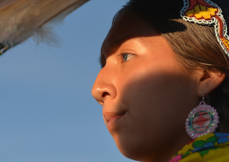 "Justin Sheely | The Sheridan Press<br /> A young dancer shades her face during the grand entry powwow Saturday evening during Crow Fair at Crow Agency, Montana. Crow Fair started in 1904 and is currently the largest gathering of Native Americans of the great plains tribes. The week-long celebration includes parades, powwow dance competitions and rodeo. For crow native Alma McCormick of Hardin, Montana, Crow Fair is an important way of preserving the culture of the Apsaalooke – people of the large-beaked bird – and acts as a family reunion of sorts for relatives living out of the reservation or out of state. It is also an event where Crow children hear their native language used, ""Your language is your culture,"" said McCormick, who has a three-year-old granddaughter who's already showing interest in the dancing. Year after year Crow Fair has imparted the cultural heritage and language of the plains tribes onto the next generation."