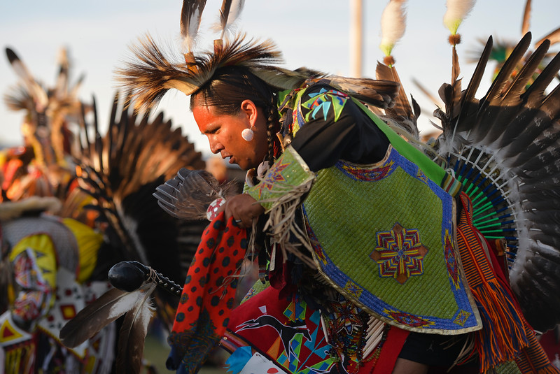 "Justin Sheely | The Sheridan Press<br /> A dancer competes in the middle of the arbor during the grand entry powwow Saturday evening during Crow Fair at Crow Agency, Montana. Crow Fair started in 1904 and is currently the largest gathering of Native Americans of the great plains tribes. The week-long celebration includes parades, powwow dance competitions and rodeo. For crow native Alma McCormick of Hardin, Montana, Crow Fair is an important way of preserving the culture of the Apsaalooke – people of the large-beaked bird – and acts as a family reunion of sorts for relatives living out of the reservation or out of state. It is also an event where Crow children hear their native language used, ""Your language is your culture,"" said McCormick, who has a three-year-old granddaughter who's already showing interest in the dancing. Year after year Crow Fair has imparted the cultural heritage and language of the plains tribes onto the next generation."