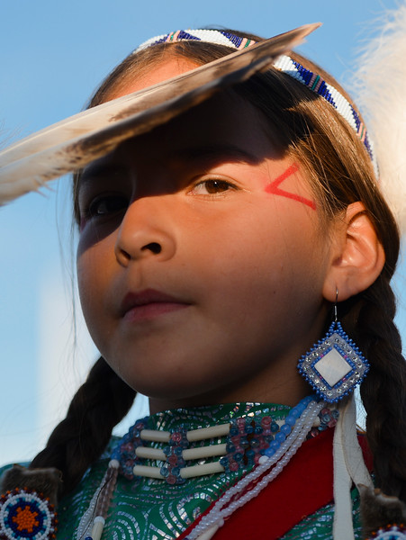 "Justin Sheely | The Sheridan Press<br /> A young dancer shields her face during the grand entry powwow Saturday evening during Crow Fair at Crow Agency, Montana. Crow Fair started in 1904 and is currently the largest gathering of Native Americans of the great plains tribes. The week-long celebration includes parades, powwow dance competitions and rodeo. For crow native Alma McCormick of Hardin, Montana, Crow Fair is an important way of preserving the culture of the Apsaalooke – people of the large-beaked bird – and acts as a family reunion of sorts for relatives living out of the reservation or out of state. It is also an event where Crow children hear their native language used, ""Your language is your culture,"" said McCormick, who has a three-year-old granddaughter who's already showing interest in the dancing. Year after year Crow Fair has imparted the cultural heritage and language of the plains tribes onto the next generation."