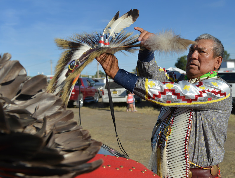 Justin Sheely | The Sheridan Press<br /> Myron Hoops of the Assiniboine Cree tribe in Fort Belknap, Montana, prepares for the grand entry powwow last August during Crow Fair at Crow Agency, Montana. Crow Fair started in 1904 and is currently the largest gathering of Native Americans of the great plains tribes. The week-long celebration includes parades, powwow dance competitions and rodeo. Year after year Crow Fair has imparted the cultural heritage and language of the plains tribes onto the next generation.