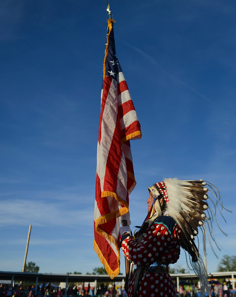 "Justin Sheely | The Sheridan Press<br /> A dancer carries the U.S. national flag into the arbor during the grand entry powwow Saturday evening during Crow Fair at Crow Agency, Montana. Crow Fair started in 1904 and is currently the largest gathering of Native Americans of the great plains tribes. The week-long celebration includes parades, powwow dance competitions and rodeo. For crow native Alma McCormick of Hardin, Montana, Crow Fair is an important way of preserving the culture of the Apsaalooke – people of the large-beaked bird – and acts as a family reunion of sorts for relatives living out of the reservation or out of state. It is also an event where Crow children hear their native language used, ""Your language is your culture,"" said McCormick, who has a three-year-old granddaughter who's already showing interest in the dancing. Year after year Crow Fair has imparted the cultural heritage and language of the plains tribes onto the next generation."