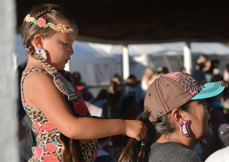 "Justin Sheely | The Sheridan Press<br /> Six-year-old Mikaylee Old Coyote, of Ethete, Wyoming, plays with her mother Heather Sun Rhodes' hair as they wait prior to the grand entry powwow Saturday evening during Crow Fair at Crow Agency, Montana. Crow Fair started in 1904 and is currently the largest gathering of Native Americans of the great plains tribes. The week-long celebration includes parades, powwow dance competitions and rodeo. For crow native Alma McCormick of Hardin, Montana, Crow Fair is an important way of preserving the culture of the Apsaalooke – people of the large-beaked bird – and acts as a family reunion of sorts for relatives living out of the reservation or out of state. It is also an event where Crow children hear their native language used, ""Your language is your culture,"" said McCormick, who has a three-year-old granddaughter who's already showing interest in the dancing. Year after year Crow Fair has imparted the cultural heritage and language of the plains tribes onto the next generation."