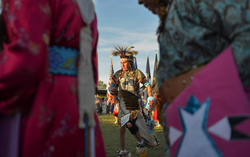 "Justin Sheely | The Sheridan Press<br /> Dancers move to the drum beat during the grand entry powwow Saturday evening during Crow Fair at Crow Agency, Montana. Crow Fair started in 1904 and is currently the largest gathering of Native Americans of the great plains tribes. The week-long celebration includes parades, powwow dance competitions and rodeo. For crow native Alma McCormick of Hardin, Montana, Crow Fair is an important way of preserving the culture of the Apsaalooke – people of the large-beaked bird – and acts as a family reunion of sorts for relatives living out of the reservation or out of state. It is also an event where Crow children hear their native language used, ""Your language is your culture,"" said McCormick, who has a three-year-old granddaughter who's already showing interest in the dancing. Year after year Crow Fair has imparted the cultural heritage and language of the plains tribes onto the next generation."