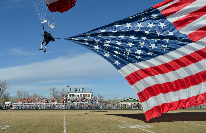 Justin Sheely | The Sheridan Press<br /> Double amputee Dana Bowman, U.S. Army Sergeant First Class, retired, glides down to the field with the national flag during the Tongue River Veterans Day Community Celebration in November at Tongue River High School. Middle school students personally wrote letters to local veterans thanking them for their service and extending an invitation to their Veterans Day event. Dana Bowman was the guest speaker for the event. Bowman lost both of his legs in a midair collision during an exercise with the Army's Golden Knights parachute team in 1994. Since that accident, he recovered and with the use of prosthetic legs, he reenlisted in the Army. Bowman is the founder of HALO for Freedom Warrior Foundation and currently performs skydive demonstrations and motivational speaking engagements.