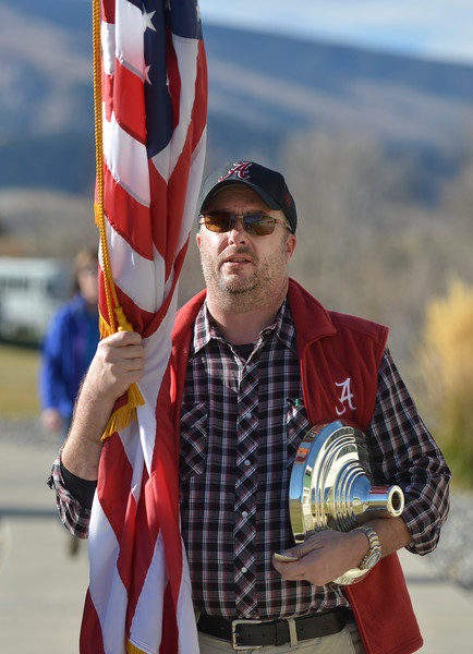 Justin Sheely | The Sheridan Press<br /> Ed Hinzman carries the national flag inside for the ceremonies during the Tongue River Veterans Day Community Celebration Tuesday at Tongue River High School. Middle school students personally wrote letters to local veterans thanking them for their service and extending an invitation to their Veterans Day event.
