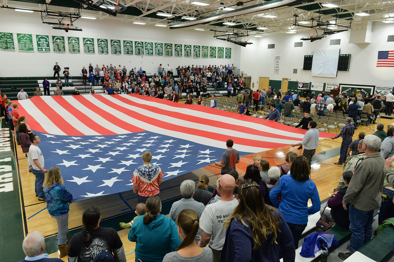 Justin Sheely | The Sheridan Press<br /> Dana Boman's national flag is stretched across the gymnasium by students during the Tongue River Veterans Day Community Celebration Tuesday at Tongue River High School. Middle school students personally wrote letters to local veterans thanking them for their service and extending an invitation to their Veterans Day event.