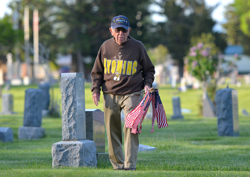 Justin Sheely | The Sheridan Press<br /> Korean War Veteran Tom Wallenzien makes sure that no veteran's grave is left without a flag during morning decorating on Memorial Day at the Sheridan Municipal Cemetery. Members of the American Legion Post #7, Veterans of Foreign Wars, Disabled Veterans and community members decorated the headstones of veterans with flags.