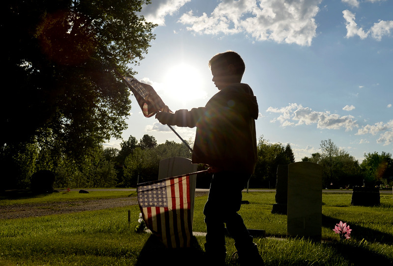 Justin Sheely | The Sheridan Press<br /> Six-year-old Hunter Bailey carries flags to grave sites with empty flag holders during morning decorating on Memorial Day at the Sheridan Municipal Cemetery. Members of the American Legion Post #7, Veterans of Foreign Wars, Disabled Veterans and community members decorated the headstones of veterans with flags.