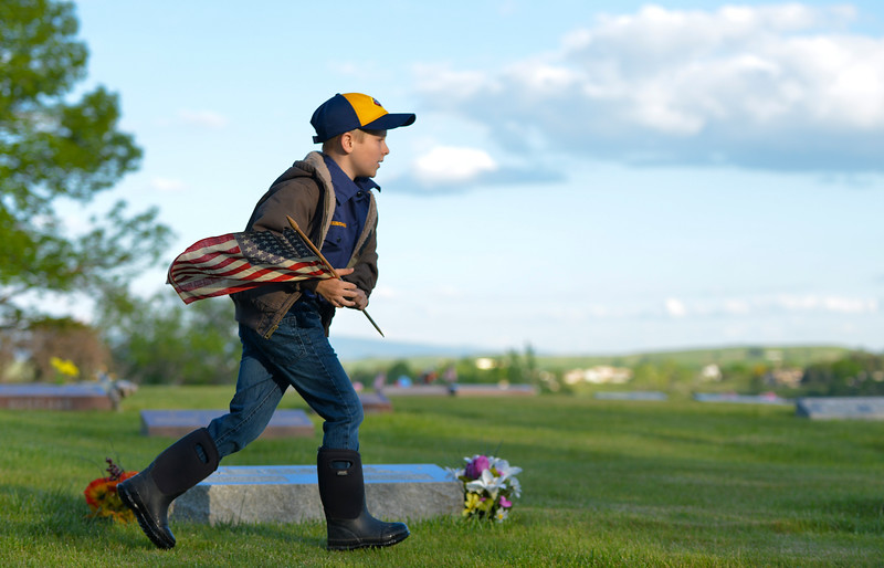 Justin Sheely | The Sheridan Press<br /> Eight-year-old Cub Scout Brigham Bailey carries flags to grave sites with empty flag holders during morning decorating on Memorial Day at the Sheridan Municipal Cemetery. Members of the American Legion Post #7, Veterans of Foreign Wars, Disabled Veterans and community members decorated the headstones of veterans with flags.
