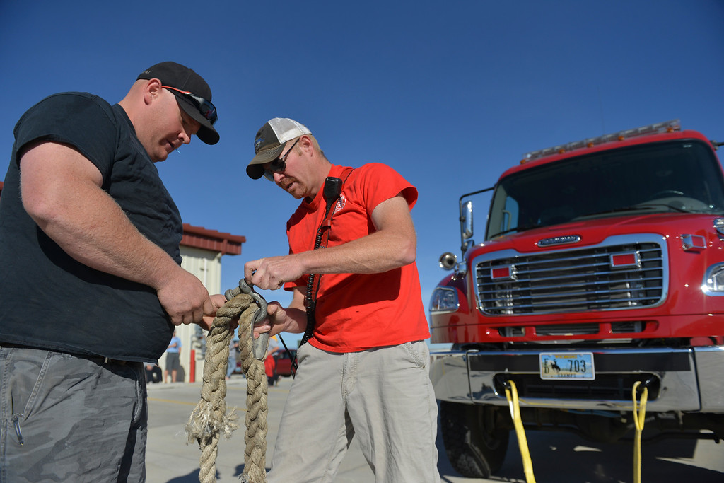 Justin Sheely | The Sheridan Press<br /> Big Goose volunteer firefighters Erik Koepp, left, and Justin Johnston connect a heavy rope to a fire truck for the inaugural fire truck pull Saturday at Goose Valley Fire Station. Members of the volunteer fire department competed against athletes from Big Horn High School football and volleyball teams to see which group could pull the 6400-pound fire engine fifteen feet in the shortest time. The firefighters beat the football team after pulling the truck in only 10.2 seconds – Rams' time was 12.25 seconds. The fire truck pull benefits the Wyoming Special Olympics and the torch run.