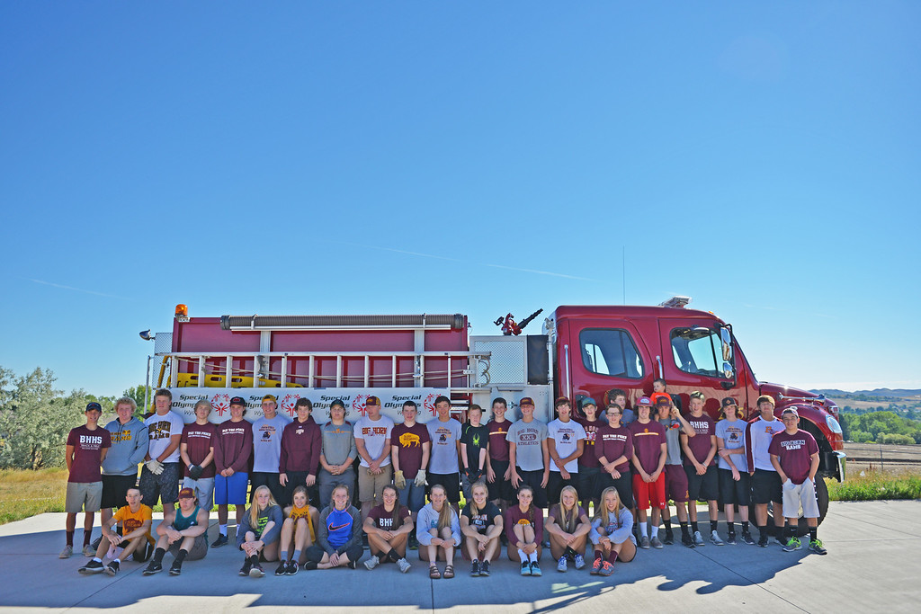 Justin Sheely | The Sheridan Press<br /> Big Horn students pose for a photo after the inaugural fire truck pull Saturday at Goose Valley Fire Station. Members of the volunteer fire department competed against athletes from Big Horn High School football and volleyball teams to see which group could pull the 6400-pound fire engine fifteen feet in the shortest time. The firefighters beat the football team after pulling the truck in only 10.2 seconds – Rams' time was 12.25 seconds. The fire truck pull benefits the Wyoming Special Olympics and the torch run.