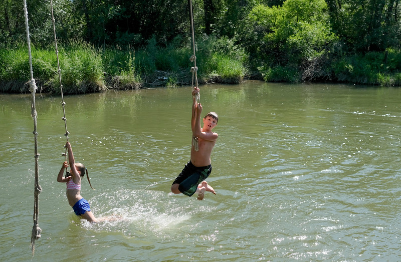 Justin Sheely | The Sheridan Press <br /> Thirteen-year-old Payton Bastrom, right, and Acacia Switzer, left, swing over the Tongue River during the Independence Day celebrations Tuesday at Connor Battlefield State Historic Site in Ranchester. The town of Ranchester hosted its annual celebration on the Fourth of July with live music from the Two Tracks, family games, food and other special events including the wife-carrying competition.