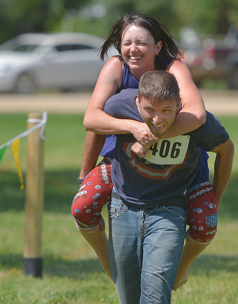 Justin Sheely | The Sheridan Press <br /> Rick Miller carries Kristina Miller across the finish line in the wife-carrying competition during the Independence Day celebrations Tuesday at Connor Battlefield State Historic Site in Ranchester.