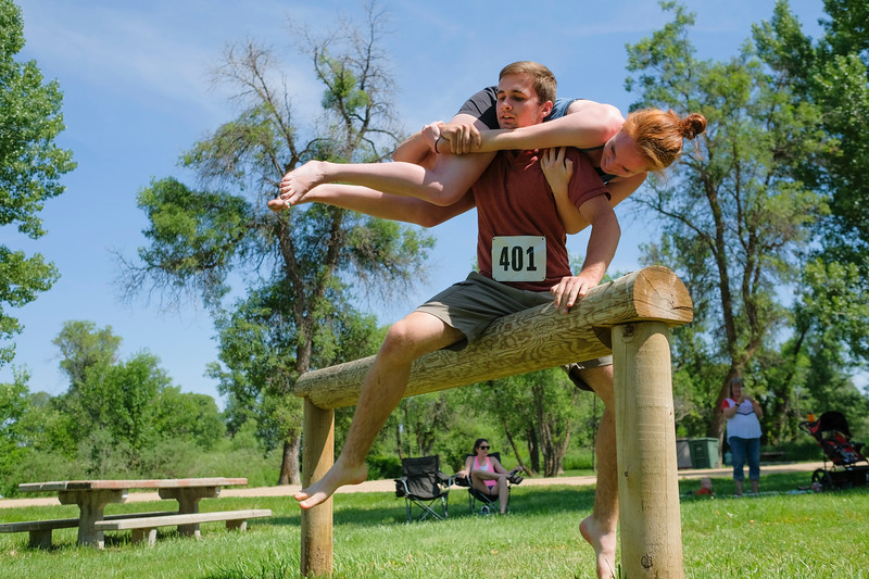 Justin Sheely | The Sheridan Press <br /> Zack Petersburg lifts Janika Sweeney over an obstacle in the wife-carrying competition during the Independence Day celebrations Tuesday at Connor Battlefield State Historic Site in Ranchester. Petersburg took first place.
